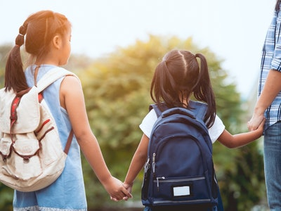 Back to school. Asian mother and daughter pupil girl with backpack holding hand and going to school together in vintage color tone