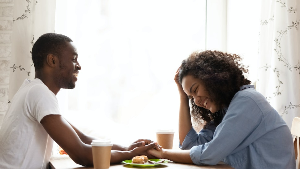 Happy smiling African American man on first date with attractive mixed race girlfriend in cafe, young couple in love laughing at funny joke together, drinking coffee, flirting, pleasant conversation
