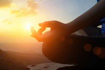 Young women meditate while doing yoga meditation, spiritual mental health practice with silhouette of lotus pose having peaceful mind relaxation on mountain outdoor with sunset golden heavenly sky.