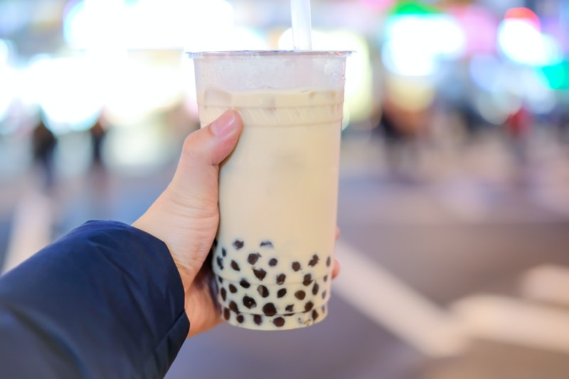 Hand holding a plastic glass of Taiwan iced bubble milk tea with Blur background,  bokeh background