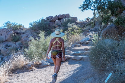 Woman Hiking Up Pinnacle Peak Desert Trail In Scottsdale, Arizona in summer time.