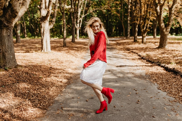 Smiling young blonde woman having fun in autumn park. Dancing in stylish red shoes and white dress.