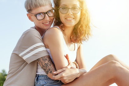 Beautiful young lesbian couple gently hugging in the sunshine, homosexual family, love and tolerance