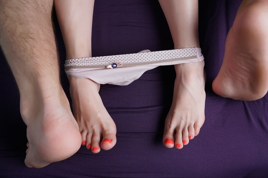 Female and male feet lie on a violet sheet. Women's panties are down on their feet. Lovers have sex.