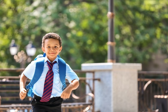 Cute African-American schoolboy running outdoors