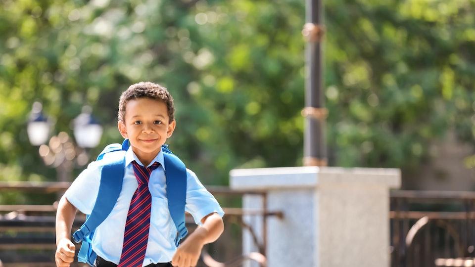Cute African-American schoolboy running outdoors