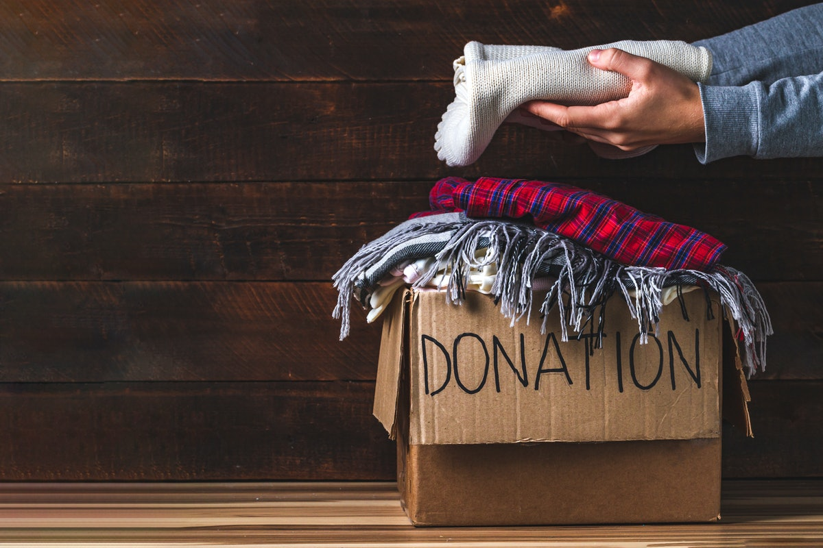 Donation concept. Donation box with donation clothes on a wooden background. Charity. Helping poor and needy people. Copy space