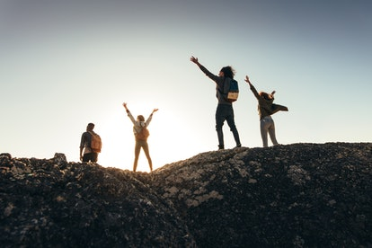 Rear view of friends having fun on mountain top and enjoying the view. Men and women standing on mountain top with their arms raised during sunset.