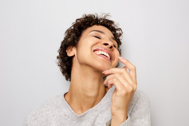 Close up portrait of happy young woman laughing with hand by head against white wall