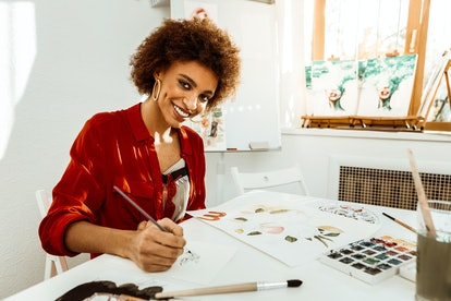 Get satisfaction. Beaming beautiful young artist gets satisfaction while drawing with watercolor