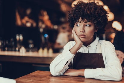 Portrait of upset waitress. She looking aside and sitting behind table while touching cheek by palm ...