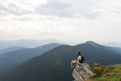 Young female hiker sits on rock in gorgeous mountain area and looks in endless horizon. Woman with tourist rusksack takes rest top of hill after reaching destination in carpathians