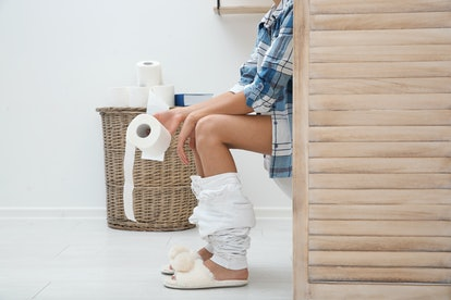 Woman with toilet paper roll behind folding screen in bathroom