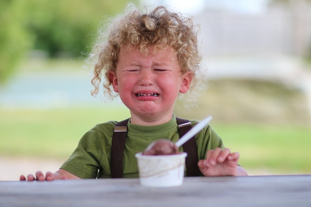 A little boy is upset, holding chocolate ice cream. The young child is visibly mad or sad.