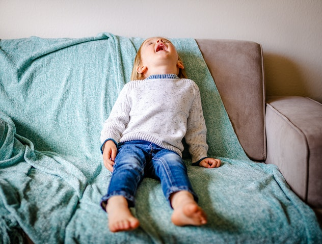 Cute toddler boy screams and cries on couch. Child is wearing blue jeans and white sweater while sit...