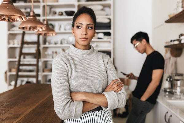 Beautiful serious african american woman holding hands together angrily looking aside with asian man with cellphone on background. Young international couple spending time on kitchen at home