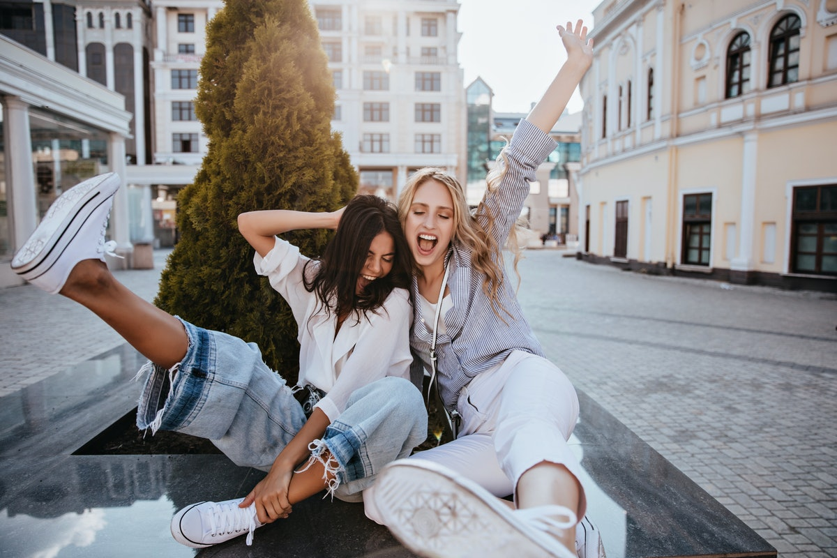 Laughing brunette woman having fun with her best friend in spring morning. Carefree sisters in good mood smiling on city background.