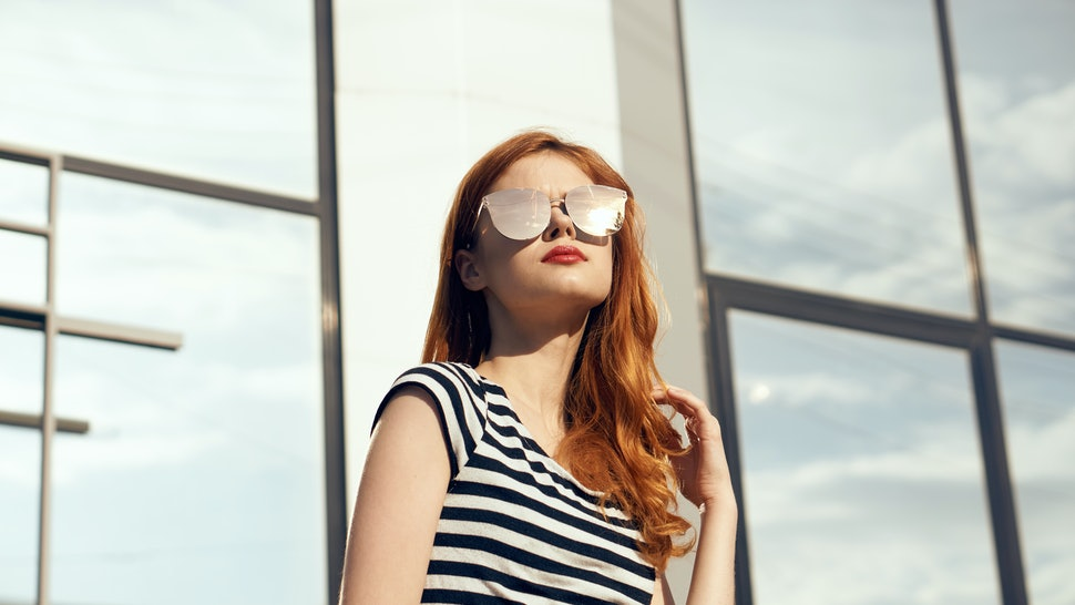 Woman in glasses, woman background, woman on mirror building background.