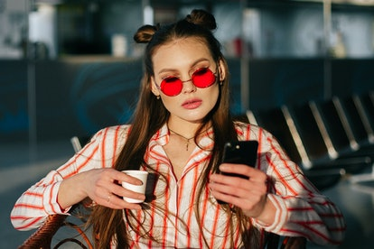 Pretty fashion model works with her smartphone sitting at the cafe in the rays of sunset