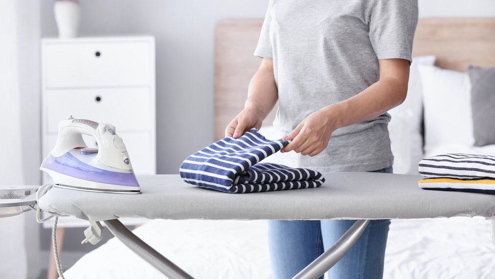 Woman folding clean clothes at home