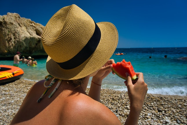 Woman female girl with hat holding and eating a slice piece of colorful red green watermelon at the beach during summer holidays. Healthy diet lifestyle in the outdoors seaside coast of spain