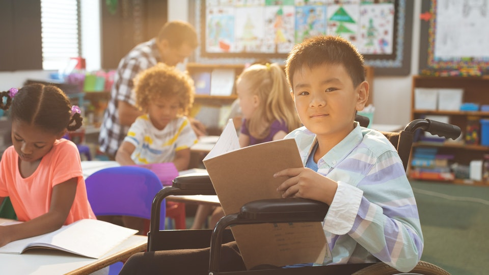 Front view of schoolboy looking at camera while sitting at desk in school  against school kids in background
