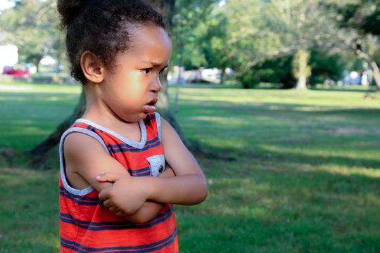 A young African American boy is unhappy at the park. His arms are crossed and his expressions shows he is angry or sad about something he sees.  Bullying concept, angry, sulking child
