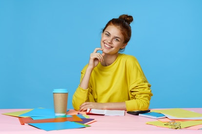 jobs woman sitting at the table on a blue background and a cup of coffee stationery