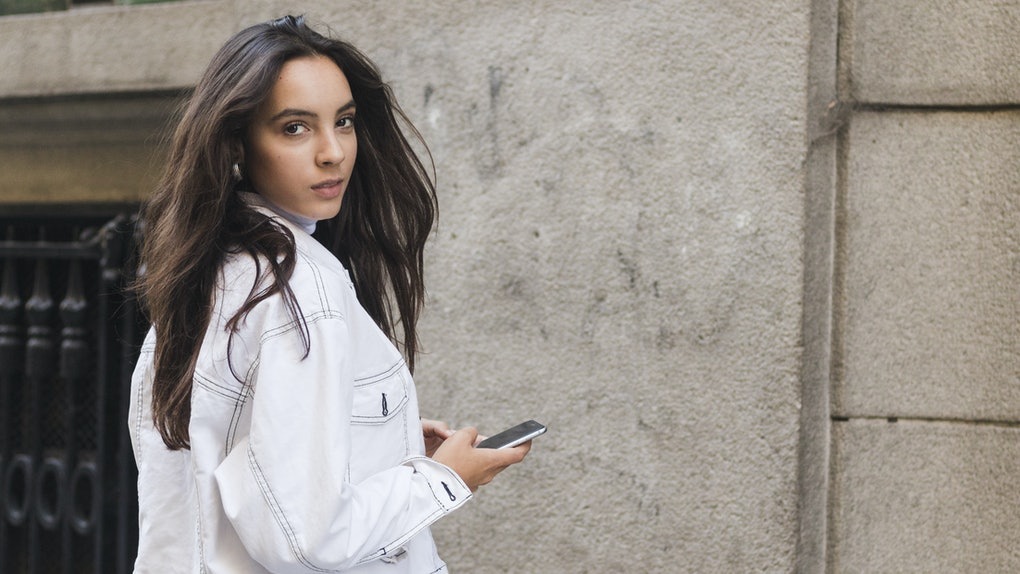 Young woman in jacket looking over shoulder holding the mobile phone in hand