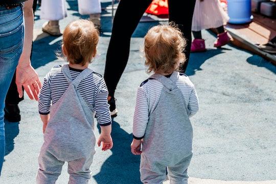 Little twin babies are walking on the street