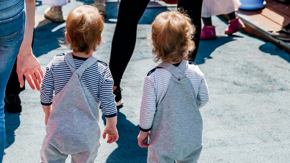 Little twin babies are walking on the street