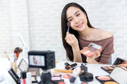 Young beautiful Asian woman professional beauty vlogger or blogger recording make up tutorial to share on social media