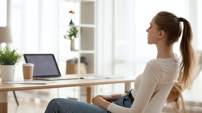 Calm peaceful young woman relaxing in office chair at workplace, tired employee sitting at desk, female student taking break after study, meditating with closed eyes, breathing deep, thinking