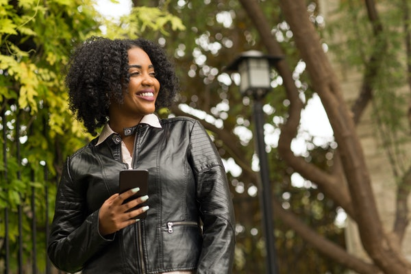 African American woman walking and texting outside.