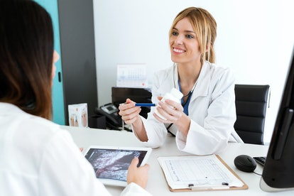 Shot of pretty young woman gynecologist doctor prescribing medication for pregnant in the medical co...