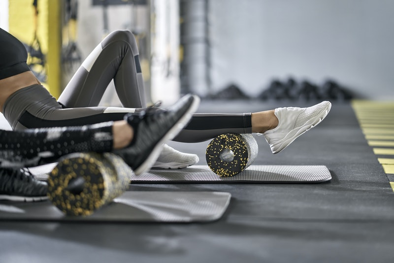 Nice girls are training with black-yellow foam rollers on the gray mats in the gym. They are wearing the multicolored sportswear: pants, tops and sneakers. Closeup. Horizontal.