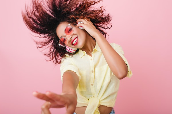 Close-up portrait of adorable curly girl happy smiling during photoshoot. Stunning african woman with light-brown skin relaxing in headphones and funny dancing on colorful background.