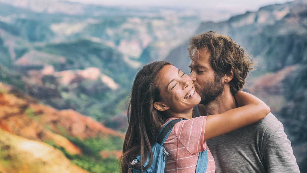 Couple in love kissing on nature travel hiking in Hawaii mountains. Young hikers people happy together. Interracial backpacking lovers kiss portrait on vacation hike.