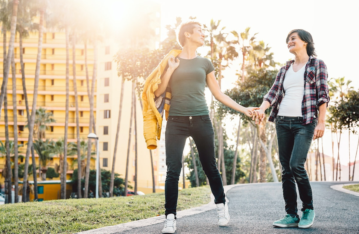 Happy lesbian couple having fun dating outdoor - Young gay women walking and holding hands outside -...