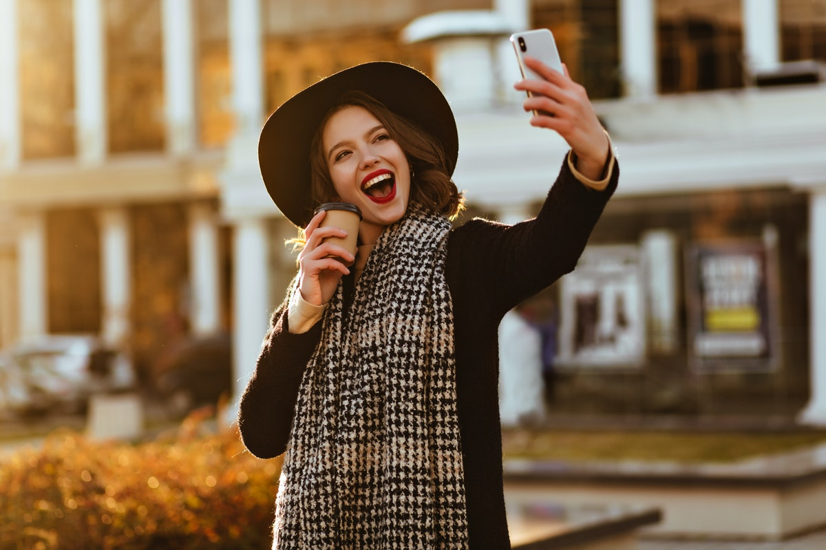 Elegant lady in coat making selfie outdoor with sincere smile. Photo of happy girl drinking coffee on the street.
