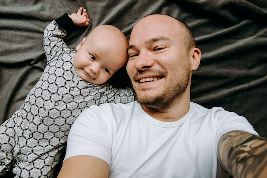 dad and baby take a selfie. They are smiling on a gray background.