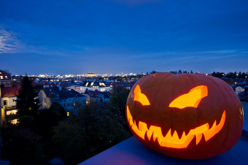 Halloween jack-o'-lantern with pumpkin face creates scary evening mood. Clear view to the cityscape of Vienna from the rooftops of the suburbs with city lights in the background.