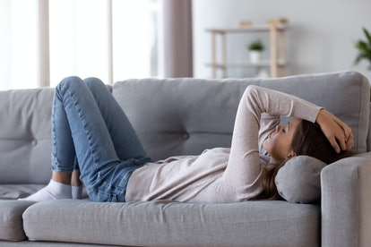 Sad depressed young woman lying on couch at home feeling headache fatigue loneliness, upset tired sick ill teen girl suffer from migraine anxiety, drowsy somnolent teenager rest on sofa after stress