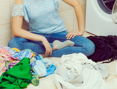 Woman in bathroom sorting dirty clothes, using to washing laundry liquid detergent. Household duties.