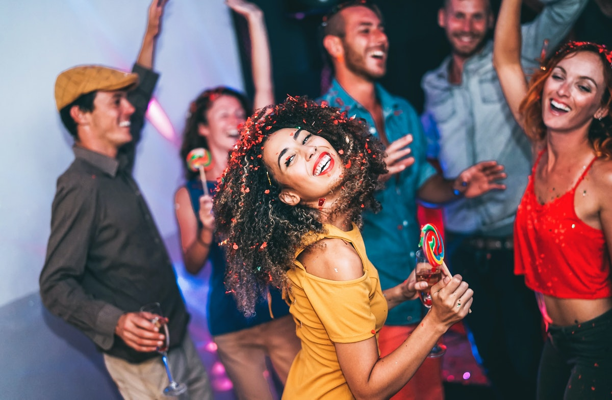 Happy friends doing party at night club - Young woman having fun with group of mates eating candy lollipops inside disco - People, friendship, nightlife and youth holidays lifestyle