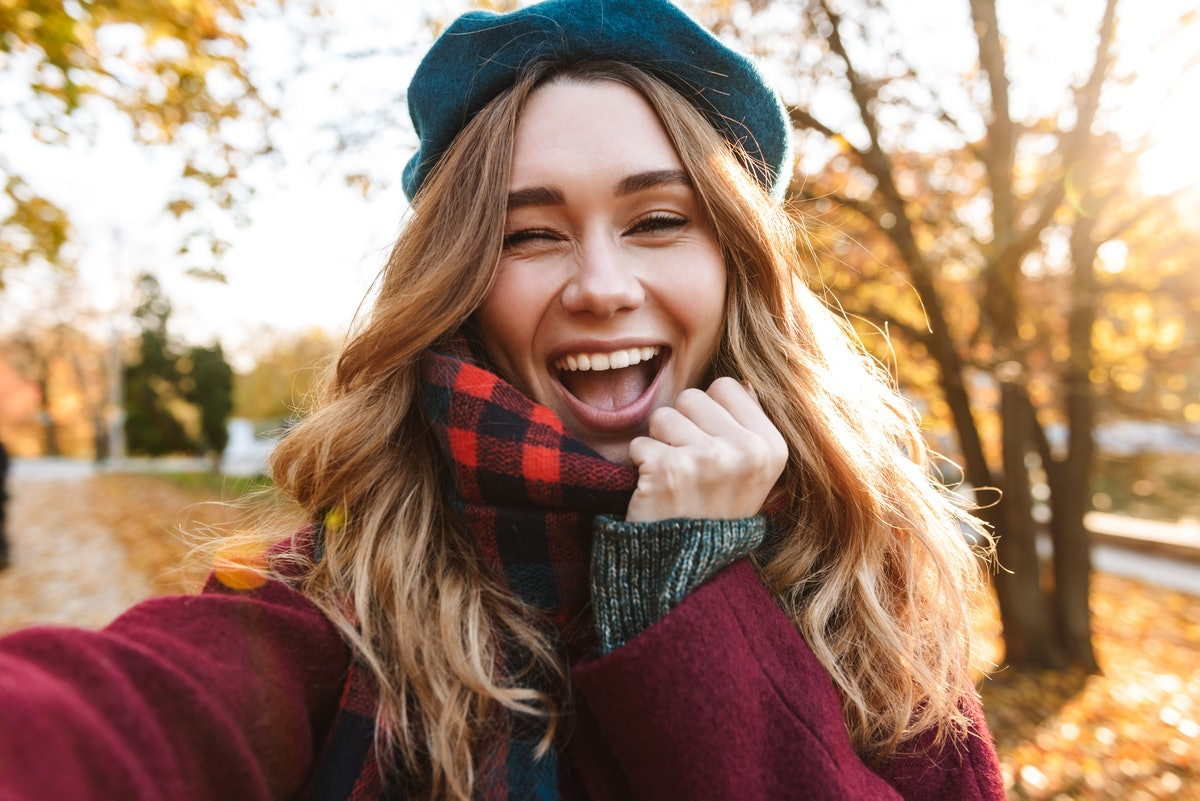 Cheerful young girl with long brown hair wearing autumn coat, walking at the park, taking a selfie