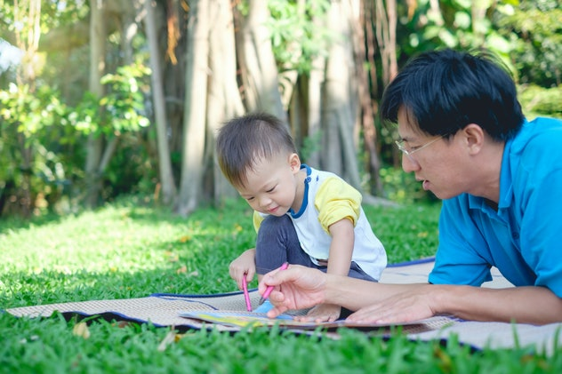 Cute little Asian 2 - 3  years old toddler boy child painting with crayons, kid coloring with father at park, Dad lying on grass spending quality time with son, Creative play for toddlers concept