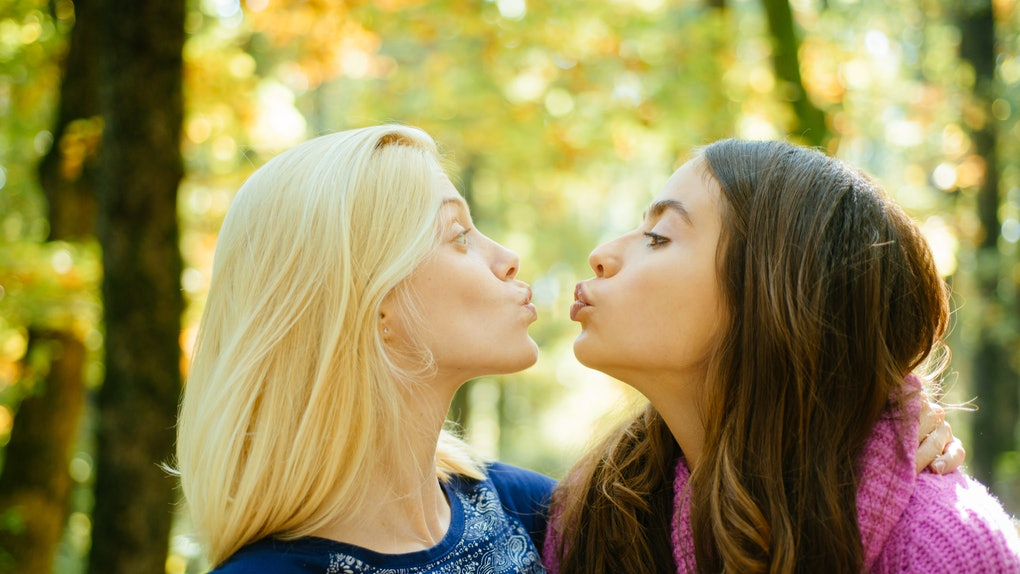 Friendly kiss. Glad to see you. Girls friends kissing. Girlish friendship concept. Blonde and brunette walking in autumn park defocused background. Women kiss cute faces close up. Come on kiss me.