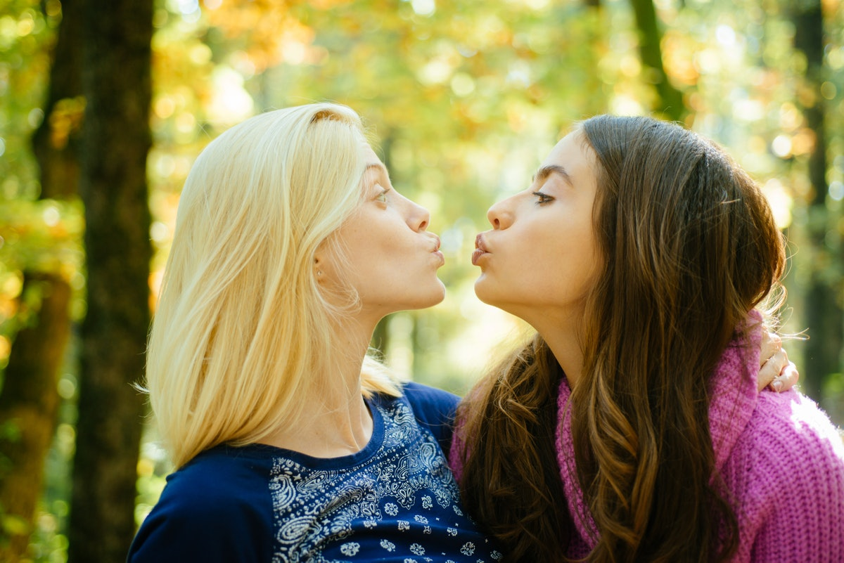 Friendly kiss. Glad to see you. Girls friends kissing. Girlish friendship concept. Blonde and brunet...