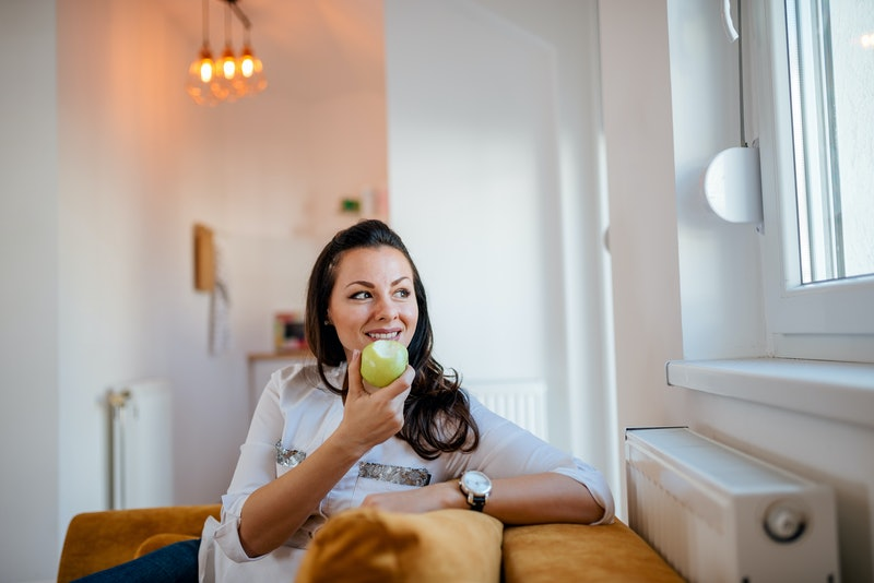 Charming woman eating apple and looking through window at home.